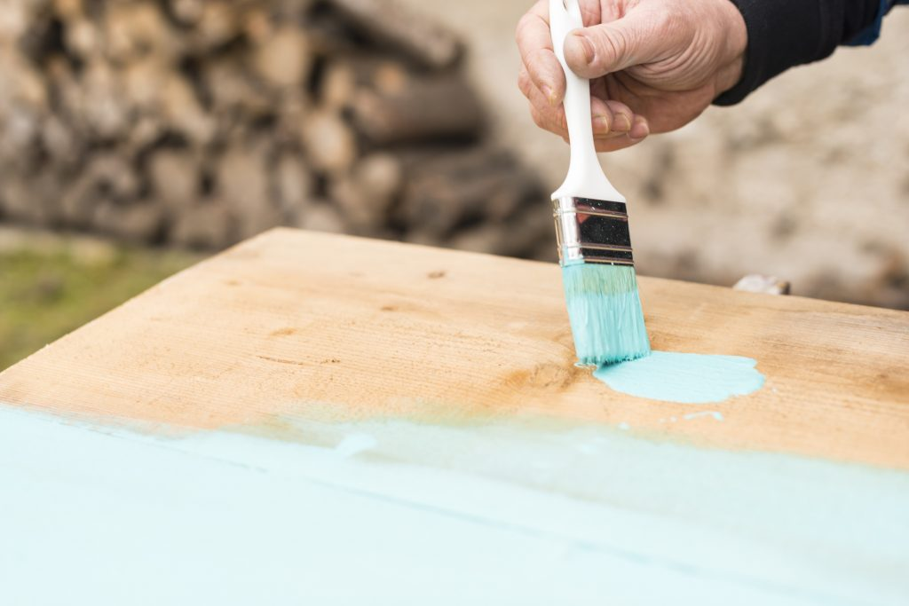 Painting a wooden plank using paintbrush