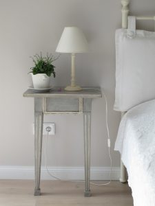 distressed shabby chic bedside table with small white lamp and plant on