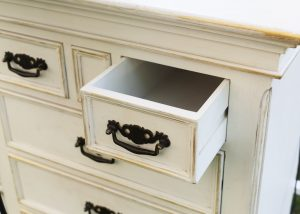 distressed chest of drawers with black handles and sanded edges