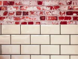 cream tiles with black grout against red brick wall.