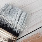 A paint brush being used to paint a hardwood floor.